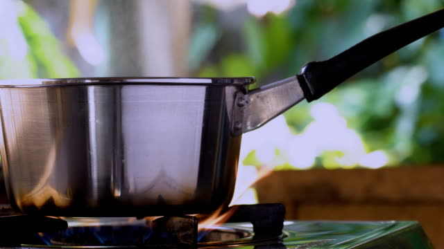 Boiling water in steel pot on the gas stove with burning in the kitchen. Close up camera movement panning shot Boiling water in steel pot on the gas stove with burning in the kitchen. Close up camera movement panning shot cooking pan stock videos & royalty-free footage