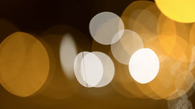 bokeh circles slowly moving over black background. defocused light leaks.  slow motion. for stylizing video, transitions. uhd, 4k - bokeh stock videos & royalty-free footage