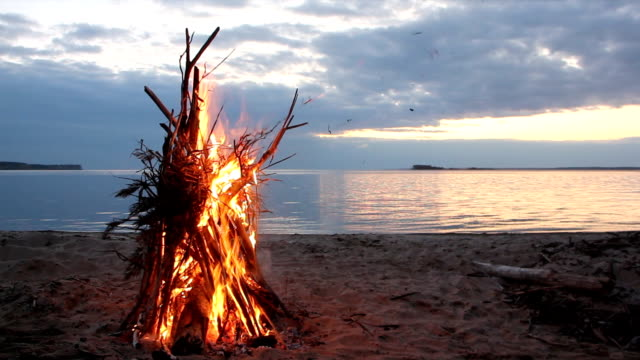 Bonfire in the form of a tent burning on the riverbank  on the sunset - video