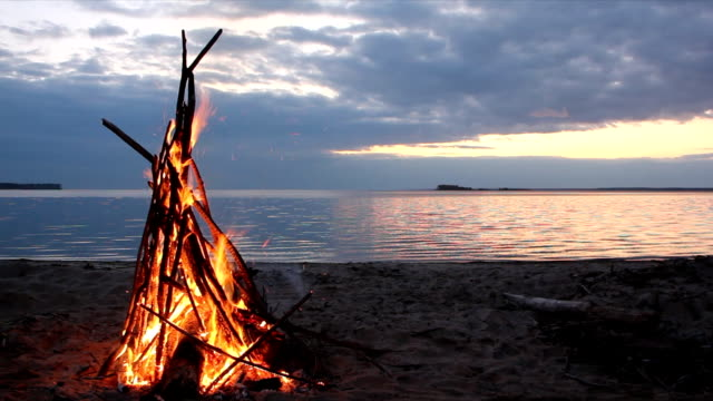 Bonfire in the form of a tent burning on the riverbank  on the sunset video