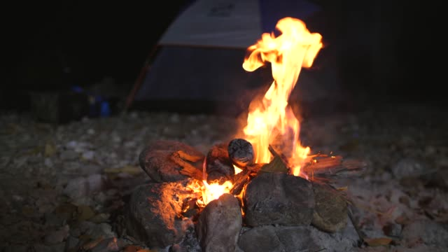 Bonfire on the Rocky Beach with Tent Background