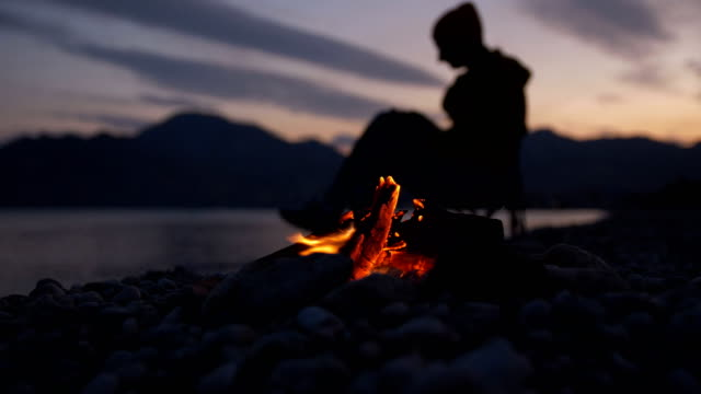 bonfire on the rocky shore of the sea against the background of a resting man sky with clouds and mountains - eastern european descent stock videos & royalty-free footage