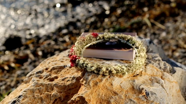 Book and wreath on the beach
