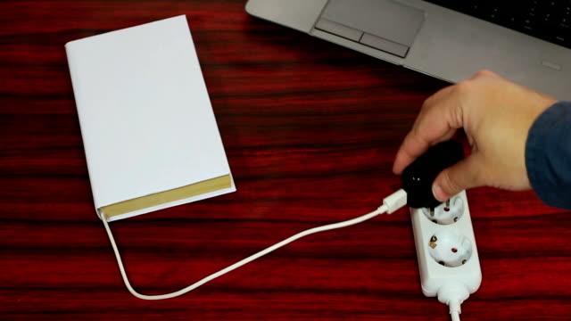 vidéos et rushes de livre relié à une prise de courant. - vidéos de rallonge électrique