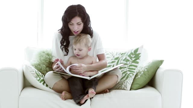 libro madre e bambino. - gambe incrociate video stock e b–roll