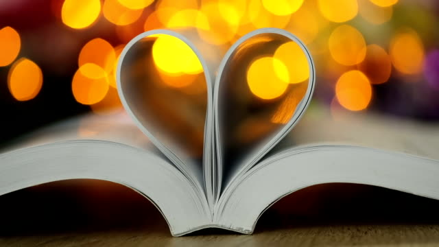 Book page decorate to heart shape with celebration bokeh light for love and romance of valentines day concept , 4K Dci resolution video