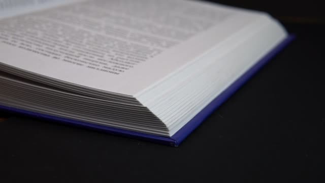 Book pages turning in slow mo