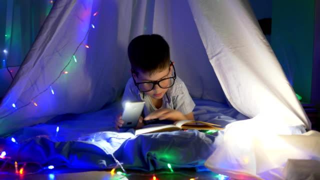 buch lesen, clever kid in brille lesen märchen in taschenlampe beleuchtung in zelt mit girlanden zu hause liegen - girlande dekoration stock-videos und b-roll-filmmaterial