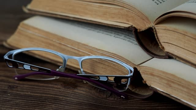 Books and glasses on wooden table Books and glasses on wooden table textbook stock videos & royalty-free footage