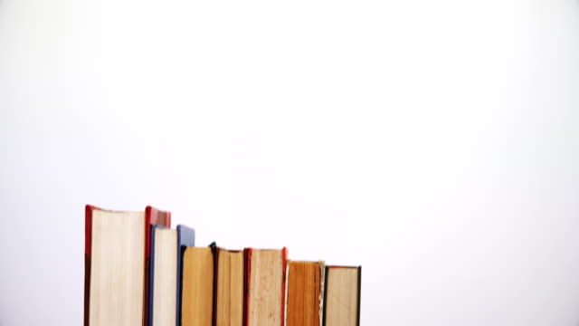 Books arranged on wooden table 4k video