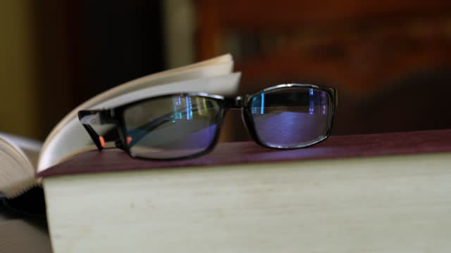 böcker, stängd och öppen bok, och läsglasögon på bordet. hem inställning. - lagbok bildbanksvideor och videomaterial från bakom kulisserna
