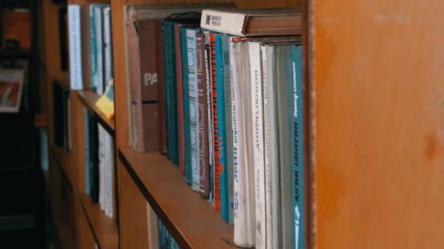 stockvideo's en b-roll-footage met boeken op de planken in de bibliotheek. stapels boeken op de planken van de oude bibliotheek - boekenkast