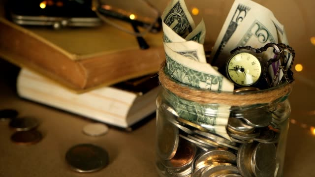 Books with glass penny jar filled with coins and banknotes. Tuition or education financing concept. Scholarship money.