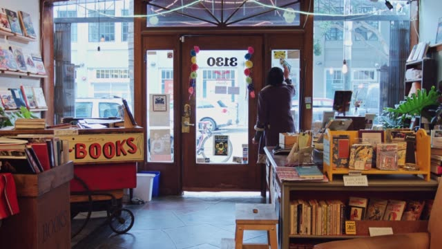 bookstore worker flipping sign to open - open sign stock videos & royalty-free footage