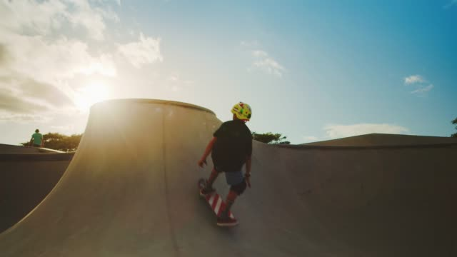 Boosting over the coping Skateboarder kid flying through the air in skate park at sunset, extreme skateboarding kid jump in slow motion skateboarding stock videos & royalty-free footage
