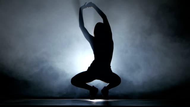vidéos et rushes de booty dance en silhouette. joué fille sportive dans studio sombre - twerk