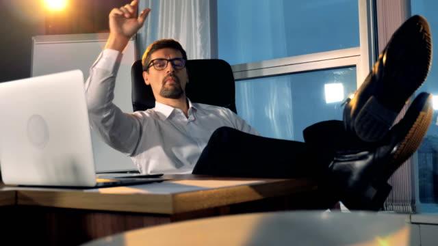 a bored businessman throws away crumpled paper balls. - nuda filmów i materiałów b-roll