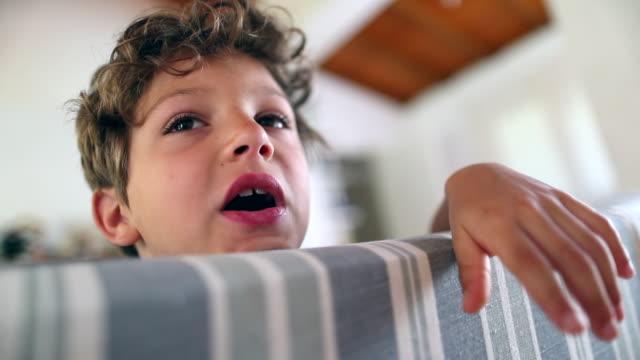 bored child boy at home with bored face - nuda filmów i materiałów b-roll