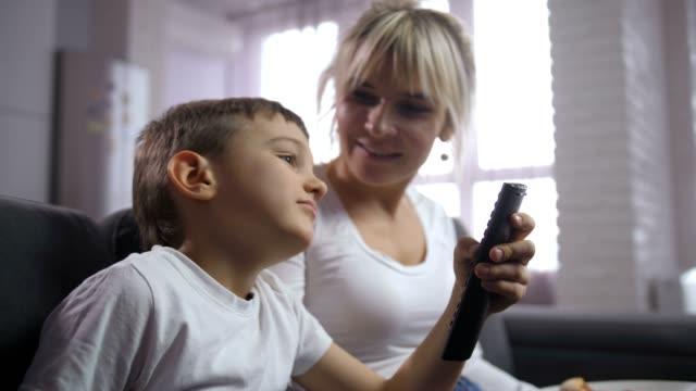 vídeos de stock e filmes b-roll de bored little boy choosing program with tv remote - tv e familia e ecrã