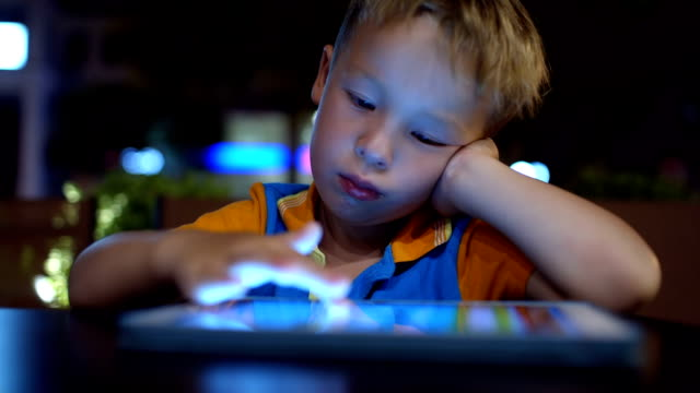Bored little boy using pad in cafe Bored little boy in cafe using touch pad without any interest padding stock videos & royalty-free footage