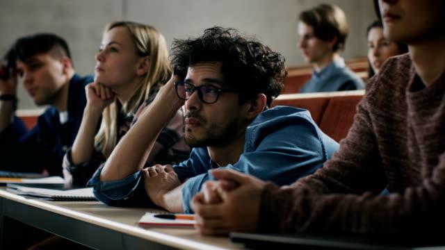 znudzony mężczyzna student słucha wykład na uniwersytecie. zmęczony, wyczerpany i przepracowany młody mężczyzna trzyma głowę. - nuda filmów i materiałów b-roll
