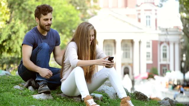uttråkad man, hans flickvän kommunicerar med någon på internet - pojkvän bildbanksvideor och videomaterial från bakom kulisserna