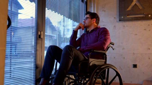 uttråkad man i rullstol tittar genom fönstret - fysiskt funktionshinder bildbanksvideor och videomaterial från bakom kulisserna