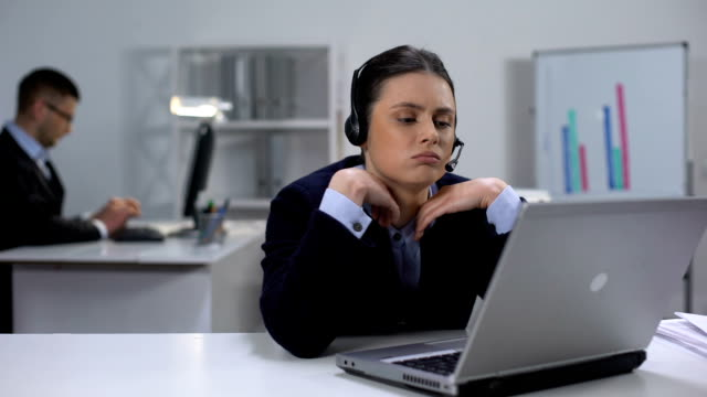 Bored operator in headset at workplace waiting for customer call, telemarketing