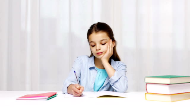 bored school girl with books writing to notebook at home video