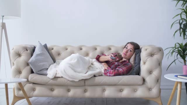 bored woman changing tv channels with remote control - nuda filmów i materiałów b-roll
