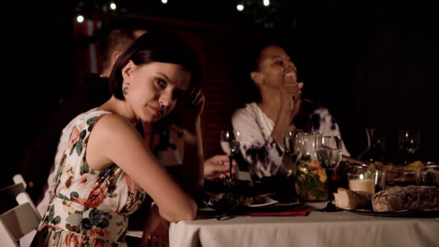 Bored woman sitting on party Dull woman feeling bored and sitting at table with friends at night. boredom stock videos & royalty-free footage