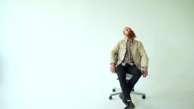 vídeos de stock e filmes b-roll de boring bearded man turning on swivel office chair on white background - chair