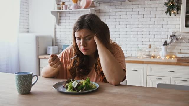 退屈なダイエット。キッチンでおいしい健康的なサラダを食べるうつ病の太りすぎの女性 - 体への関心点の映像素材/bロール