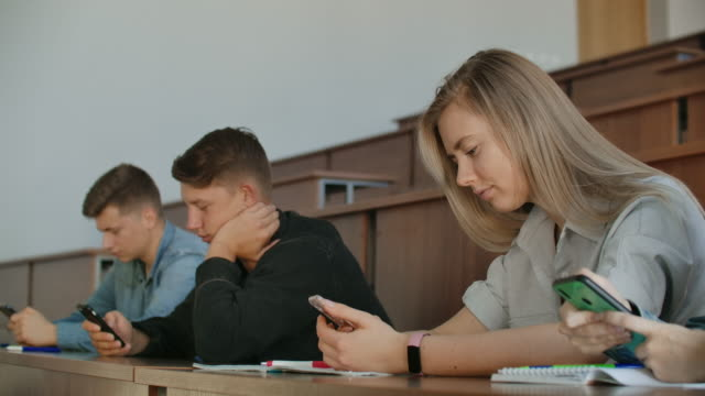 A boring lecture at the university, students look at the screens of smartphones. Many people