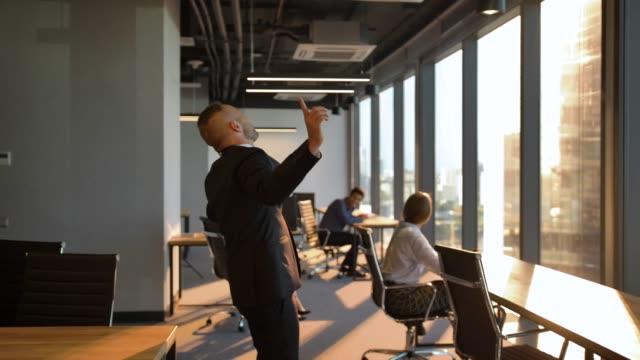Boss danse folle par la fenêtre dans le bureau pendant le coucher du soleil - Vidéo