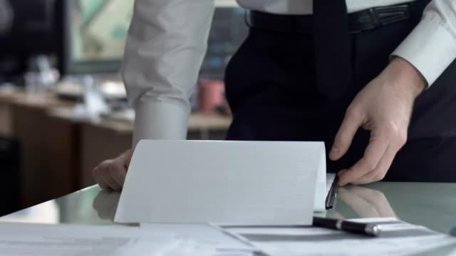 vídeos de stock, filmes e b-roll de chefe, olhando através de contrato com a xícara de café enquanto secretário digitação para trás - assistente jurídico