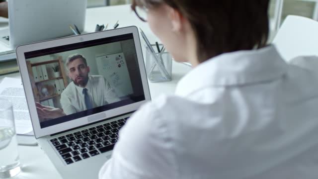 chef im gespräch mit arbeitnehmerin über online-aufruf - webinar stock-videos und b-roll-filmmaterial