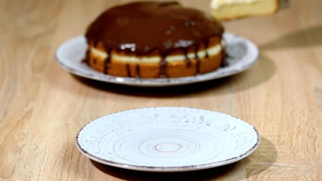boston cream pie with chocolate glazing. put it in the bowl a piece of boston cream pie. - nadziewany placek filmów i materiałów b-roll