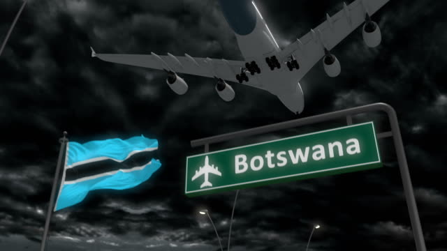 Botswana, approach of the aircraft to land Botswana, approach of the aircraft to land at night in cloudy weather, flying over the name of the country and its flag botswana stock videos & royalty-free footage