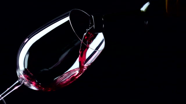 Bottle and glass with red luxury wine, black, closeup, slowmotion Bottle and glass with red luxury wine, expensive alcohol, on black background, closeup, slowmotion red wine stock videos & royalty-free footage
