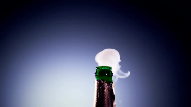 vídeos de stock e filmes b-roll de bottle champagne wine is opened. slow motion, lit background - champanhe