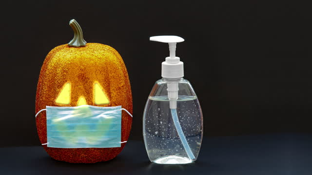 A bottle of a hansanitazer and facemask with halloween decoration background. Concept: Halloween during a pandemic, covid-19, coronavirus. A bottle of a hansanitazer and facemask with halloween decoration background. Concept: Halloween during a pandemic, covid-19, coronavirus. halloween covid stock videos & royalty-free footage