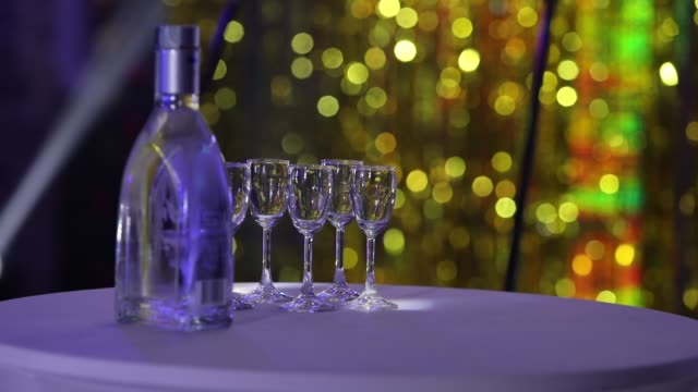 Bottle of liquor on the table, a bottle of vodka and wine glasses on a buffet table video