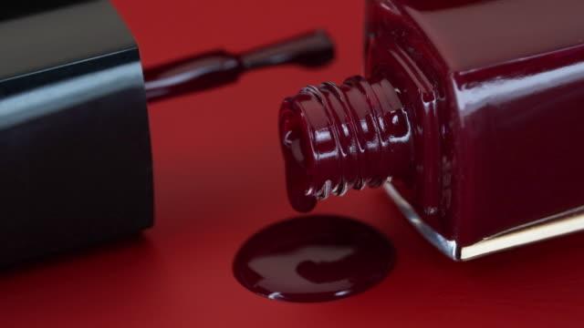 flaska nagellack ligger på röd bakgrund. - nagellack bildbanksvideor och videomaterial från bakom kulisserna