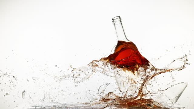 bottle of pink wine breaking and splashing against white background, slow motion 4k - getty filmów i materiałów b-roll