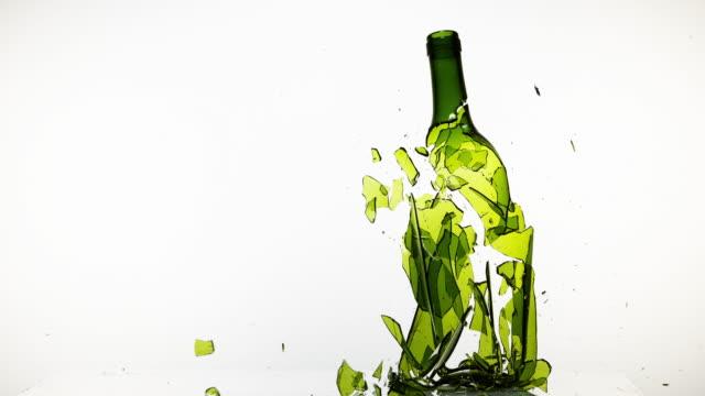 bottle of white wine breaking against white background, slow motion 4k - getty filmów i materiałów b-roll