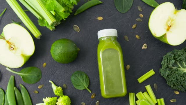 vídeos de stock e filmes b-roll de bottle with green juice and vegetables on table - sumo