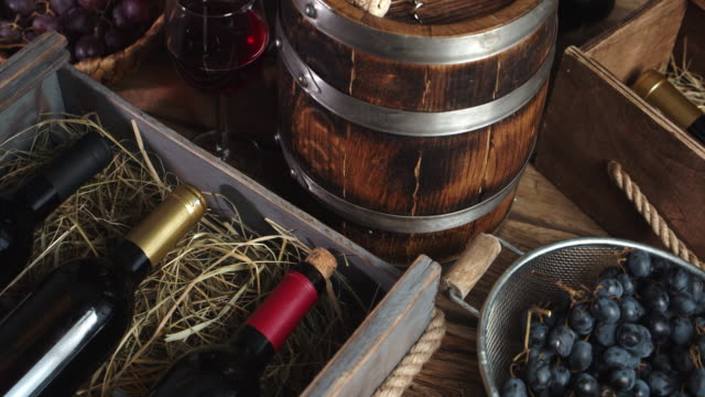 Bottles of wine in a wooden box with straw on the table.