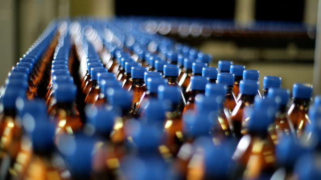 bottles on a conveyor belt factory - ripetizione video stock e b–roll