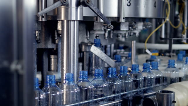 Bottles transferred from a conveyor to a filling machine. video
